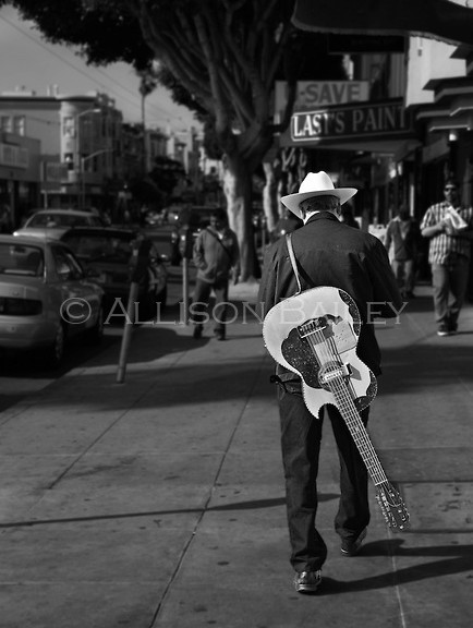 Man walks down Mission Street with his guitar slung over his back, Mission District, San Francisco, CA